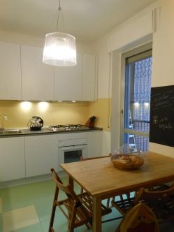 il rivestimento cucina proseguen dopo la porta finestra in un fascia realizzata con pittura lavagna